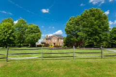 Single Family Georgian House Home Lawn Fence USA. Single family house on large plot of land in suburban Maryland.  Georgian/Colonial Style. Rail fence in Stock Photo