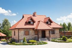Single family house of brick. With red roof over blue sky Royalty Free Stock Image