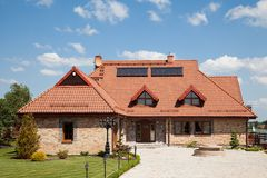 Single family house of brick. With brown roof over blue sky Stock Image