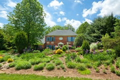 Single Family House Home Flower Landscaped Garden. Single family house on large plot of land in suburban Maryland.  Landscaped berm in front for privacy Royalty Free Stock Photography