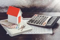 Single family house on pile of money Stock Images