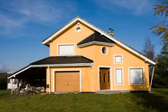 Single family small house. Single family small yellow house against blue sky royalty free stock image