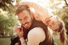 Father and daughter in park. Single father carrying her daughter on shoulders. Little girl looking at camera royalty free stock photo