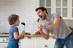 Father dancing with son holding kitchen spoon like microphone singing