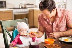 Single father feeding his baby daughter at home Stock Images