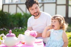 Cute little princess playing tea party with her loving father. Stock Images
