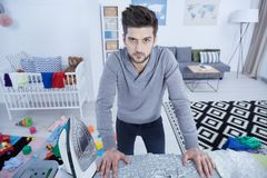 Single father ironing. Tired single father ironing children clothes in nursery royalty free stock image