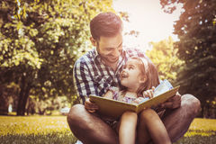 Single father sitting on grass with little daughter. Single father sitting on grass with little daughter and reading book story. Little girl sitting on father Royalty Free Stock Image