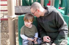 Single Father and Son. Single dad, father and son sharing a special moment at the playground Stock Image