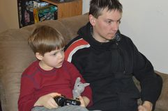 Single father and son play video games royalty free stock photo