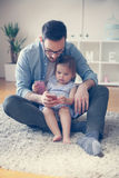 Single father wit his daughter using smart phone. Father and little baby watching something funny at smart phone Stock Photo