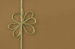 Single festive gold ribbon bow. On plain brown background with room for your text Royalty Free Stock Photos