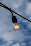 Single filament bulb against a cloudy sky Stock Photos
