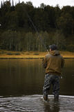 Single fisherman on a calm river is autumn fishing Stock Image