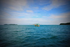 Single fishing boat in the middle of sea. Vignette-style photo of a Single fishing boat in the middle of sea royalty free stock images
