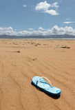 Single flip-flop on beach. Beach with flip-flop in the foreground and distant mountains in the background Royalty Free Stock Photo
