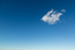 Single fluffy white cloud against deep blue sky Royalty Free Stock Image