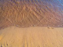 Single footprint in the sand on the beach near the waves royalty free stock image