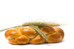 Single fresh bun and ear of wheat stock photo