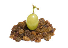 Single fresh grape on the pile of raisins isolated. Over white background Stock Photo