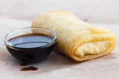 Single fried vegetable spring roll on wax paper. Stock Photo