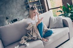 Single frustrated exhausted woman is sitting on a sofa in a living room covered with a plaid, surrounded with paper tissues, she stock image