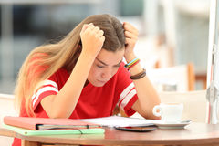 Frustrated student trying to understand notes in a bar. Single frustrated student girl trying to understand notes sitting in a bar stock photo