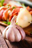 Single garlic bud with violet skin in front of few skewers Royalty Free Stock Image