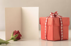 Single Gift Box with Red Rose and Card. A single small square gift box with lid, tied to a bow with gingham ribbon on a white table with a rose and an opened Royalty Free Stock Image