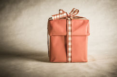 Single Gift Box Tied with Bow. A solitary, old vintage styled shot of a desaturated red Christmas gift box with lid, tied with a bow in gingham (checked) ribbon Royalty Free Stock Photography