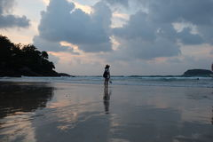 Single girl on the beach of Puket Thailand. Magnificent cloudy day. vast beach has one little girl.  looking at vast sea water Royalty Free Stock Photo