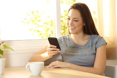 Single girl chatting on a mobile phone at home. Single girl chatting on a mobile phone sitting in a table at home stock photo
