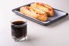 Single glass of cola drink with two hot dog fast food junk fresh sausage cheese sauce isolated on baking tray white background. Close up royalty free stock images
