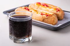 Single glass of cola drink with two hot dog fast food junk fresh sausage cheese sauce isolated on baking tray white background. Close up stock image