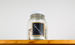 Single glass jar on wooden shelf for saving money Royalty Free Stock Photography