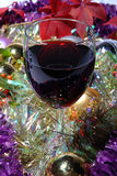 Single glass of red wine on a Christmas background. With tinsel and baubles stock photos