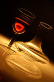 Single glass of red wine with glass decanter. Single glass of wine with red wine and decanter on a dark background with transparency stock photos
