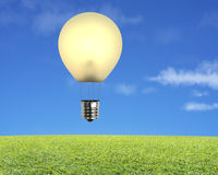 Single glowing lamp balloon flying over green meadow with sky Royalty Free Stock Images