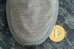 Single gold Litecoin left under a grey shoe Royalty Free Stock Image