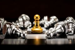 Single gold pawn chess surrounded by a number of fallen silver c. Hess pieces , business strategy concept royalty free stock images