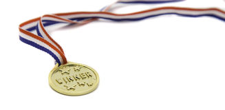 Single Gold Winner medal. A gold winner medal isolated against a white background Royalty Free Stock Image