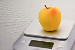 Single golden apple on a kitchen scale. Diet concept with an apple on a kitchen scale Royalty Free Stock Photos
