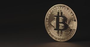 Single golden bitcoin coin reflecting light.  Wealth, digital, virtual, currency, and cryptocurrency concept