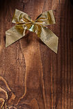 Single golden christmas bow with small bell on old wooden board Royalty Free Stock Photos
