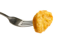 Single golden deep-fried battered chicken nugget on a fork isola Royalty Free Stock Photo