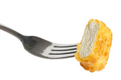 Single golden deep-fried battered chicken nugget on a fork isola Royalty Free Stock Photos