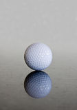 Single golf ball reflection. Single golf ball reflecting off a shiny marble surface royalty free stock photos