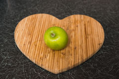Single Green Apple on Heart Shaped Chopping Board. On a black kitchen surface Stock Images