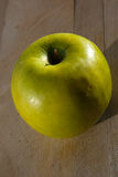 Single green apple on a wooden board Stock Photo