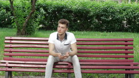 Single guy sitting on a bench with a mobile phone in the hands. A young single guy sitting on a bench with a mobile phone in the hands stock footage